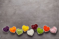 Love for healthy food concept. With little heart-shaped white bowls of grated vegetables of different colors in a row on grey surface background with copy space Stock Photo
