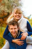 Man giving piggyback ride to woman in park Stock Photos