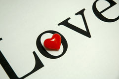 Love and heart. A red heart on a paper with letter love Stock Photography