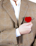 Love heart. Man in brown jacket holding a red heart at the pocket Stock Images