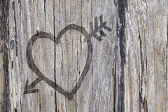Love heart and arrow graffiti carved into wood Royalty Free Stock Photos