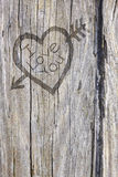 Love heart and arrow graffiti carved into wood Stock Photos