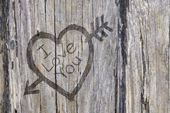 Love heart and arrow graffiti carved into wood Stock Images