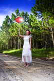 Love Heart Balloons. Woman Holds Up Two Love Heart Balloons While Standing In A White Dress On A Pine Forest Road Royalty Free Stock Images