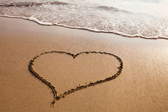 Love. Heart drawn on the sandy beach, valentines day background Stock Photo