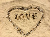 LOVE and HEART figures on a sand. Made with hands Royalty Free Stock Photography