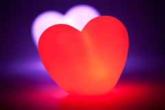 Love heart glowing red with heart behind Stock Photos