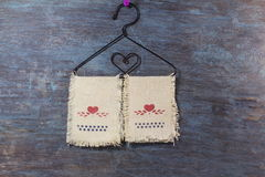 Love heart icon on fabric hanging on hanger in old wooden background Royalty Free Stock Images