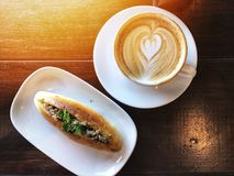 Love heart Latte art coffee in white cup and bread. In white dish on the wooden table. Wake up and full fill energy, top view. top view breakfast Stock Image