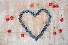 Love heart made of blueberries and widespread cherries. Love heart made of big blueberries and widespread red cherries on vintage wooden background royalty free stock images