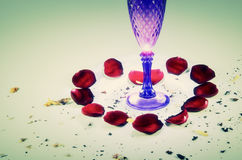 Love heart made by red roses petals and a glass Royalty Free Stock Photography