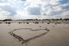 Love. Heart made in sand at sunny summer day Stock Image