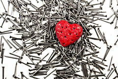 Love heart on pile of iron nails. Love heart on pile of iron grey nails royalty free stock photography