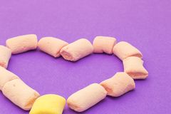 Love heart with marshmallows. Love heart with pink and yellow marshmallows royalty free stock images