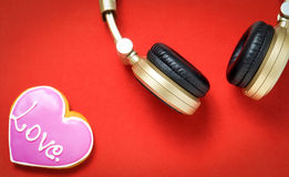 Love Heart on red background with Golden headphone. Royalty Free Stock Photography