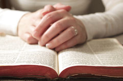 Hands on Religious Bible. Close up of the bible with a women reading the bible and her hands resting on the book royalty free stock photography