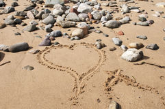 Love Heart on Sandy Beach. Love heart and kiss written in sand on pebble beach Royalty Free Stock Photos