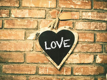 Love on heart shape chalk board, with vintage brick wall.  stock images