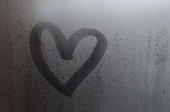 Love heart shape hand drawn on wet, frozen window pane with morning sunlight background. Selective focus macro picture.  royalty free stock photography