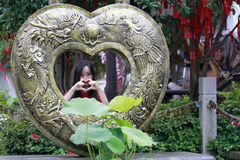 Love heart shape and wishing tree. In Feng Jing ancient town, there is a love heart shape which is made of copper, with dragon and phoenix pattern. a girl stand Stock Image