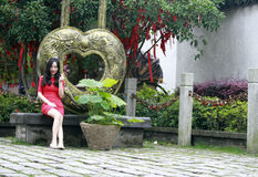 Love heart shape and wishing tree. In Feng Jing ancient town, there is a love heart shape which is made of copper, with dragon and phoenix pattern. a girl sit by Royalty Free Stock Photography