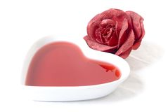 Love #3. A heart-shaped dish with red liquid and a rose Stock Images