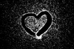 Love heart symbol drawing by finger on white salt powder on black board background royalty free stock photos
