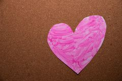 Love heart symbol painted pink. On a cork board royalty free stock photography