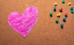 Love heart symbol painted pink on a cork board. With pins on the right side royalty free stock photo