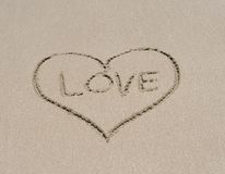 Love heart symbol in sand on tropical beach Royalty Free Stock Images