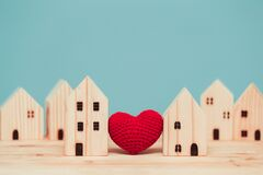 Love heart between two house wood model for stay at home for healthy community together concept