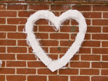 Love Heart on wall made from snow. Home is were the heart is Stock Photos