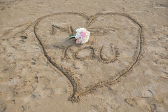 Love heart and wedding boquet. A heart shape carved into beach sand with a wedding bouquet in the sand after a small beach wedding Stock Image