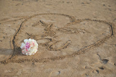 Love heart and wedding boquet. A heart shape carved into beach sand with a wedding bouquet in the sand after a small beach wedding Royalty Free Stock Image