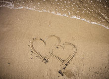 Love hearts. Two hearts drawn in the sand Stock Images