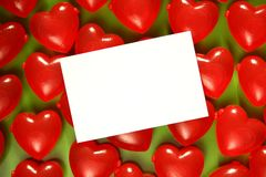 Love Hearts. Red plastic love hearts on a green background royalty free stock photography