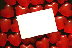 Love Hearts. White card and red plastic love hearts on a black background royalty free stock photography