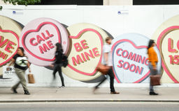 Love Hearts: Coming Soon. LONDON, UK - 11 JUNE 2014: Deliberate motion blur on shoppers walking by adversiting hoarding for a familiar UK sweet (candy) brand stock images