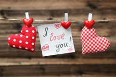 Love hearts hanging on rope on the brown wooden background Royalty Free Stock Photos