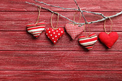 Love hearts. Hanging on a tree branch on a red wooden background Stock Photo