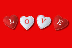 Love hearts on red background. Spelling LOVE Royalty Free Stock Images