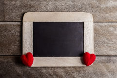 Love hearts shape and empty chalk board on wood background. Valentines day greeting card stock image