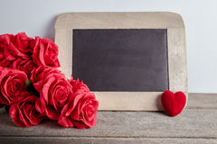 Love hearts shape, red roses and empty chalk board on wood background. Valentines day greeting card stock photography