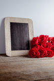 Love hearts shape, red roses and empty chalk board on wood background. Valentines day greeting card stock photo