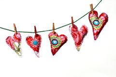 Love hearts on washing line. Red patterned textile love hearts hanging from washing line, isolated on white background stock images