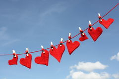 Love hearts on washing line. Row of red felt love hearts on washing line, blue sky background Royalty Free Stock Photo