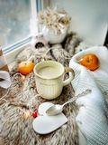 Love holiday concept. Cozy hygge composition on windowsill. Cup of coffee, spoon, wooden heart, tangerines, knitted sweater on fur fabric. Still life or lady stock photo