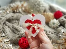 Love holiday greeting card. White and red heart in woman hand on cozy hygge background. royalty free stock images