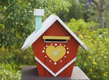 Love House in the Country. This is a model house used as a mail box. The house is rustic and colorful. On the front is a big heart. The background is countryside royalty free stock photo