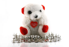 Love hurts. Teddy bear on many thumbtack stock image